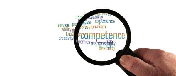 Eine Lupe schwebt über bunter Schrift. Hervorgehoben ist das Wort competence.