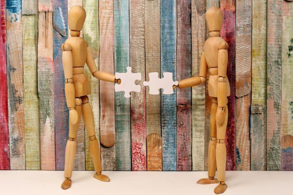 Die Graphik zeigt zwei Holzfiguren (in menschlicher Form), die jeweils ein Puzzleteil in der Hand halten. Die Puzzleteile werden von den Figuren zusammengehalten und es zeigt sich, dass sich beide Puzzleteile ineinander fügen.